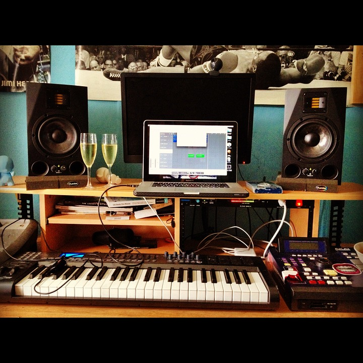 Music production center with a piano, keyboard, and laptop.